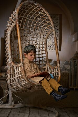 Little muslim boy in prayer cap and arabic clothes with rosary beads reading holy Koran book praying to Allah, ramadan kareem concept kid spiritual peaceful moment inside eastern traditional interior Stockfoto - 140525343