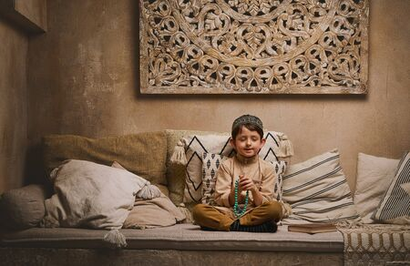 Little muslim boy in prayer cap and arabic clothes with rosary beads reading holy koran book praying to Allah, prophet Muhammad holy spirit religion symbol concept inside eastern traditional interior Banque d'images