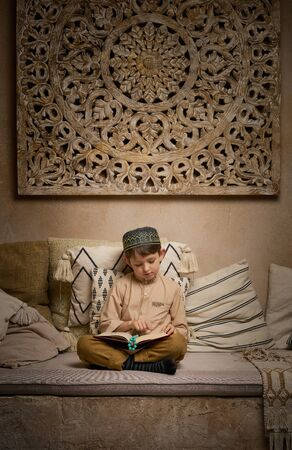 Little boy in prayer hat and arabic clothes with rosary beads reading holy koran book praying to Allah, prophet Muhammad holy spirit religion symbol concept inside eastern traditional interior