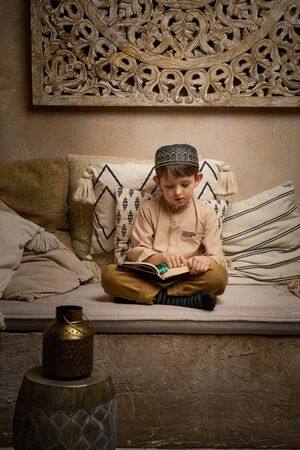Little muslim boy in prayer cap and arabic clothes with rosary beads reading holy quran book praying to Allah, ramadan kareem concept kid spiritual peaceful moment inside eastern traditional interior Banque d'images