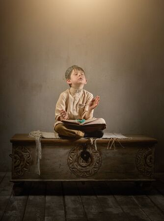 Boy in arabic clothes with rosary beads reading holy quran book praying to Allah, prophet Muhammad holy spirit religion symbol concept inside eastern traditional interior