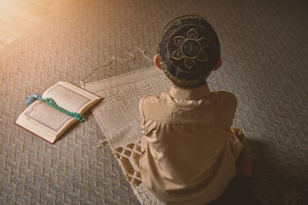 Muslim boy praying to Allah, ramadan kareem child in prayer cap and arabic clothes with rosary beads spiritual peaceful moment faith hope concept