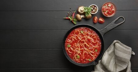 Homemade spaghetti with tomato sauce in cast iron pan served with red chili pepper, fresh basil, cherry-tomatoes and spices over black rustic wooden background, food cooking concept