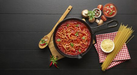 Cooking pasta with tomato sauce in cast iron pan served with chili pepper, fresh basil, cherry-tomatoes and spices over black rustic wooden background, ingredients food concept Stockfoto - 149400223