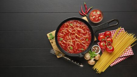 Cooking spaghetti with tomato sauce in cast iron pan served with red chili pepper, fresh basil, cherry-tomatoes and spices over black rustic wooden background. Stockfoto - 149400224