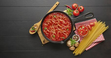 Cooking homemade pasta spaghetti with tomato sauce in cast iron pan served with red chili pepper, fresh basil, cherry-tomatoes and spices over black rustic wooden background.