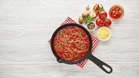 Cooking homemade pasta with tomato sauce in cast iron pan served with chili pepper, fresh basil, cherry-tomatoes and spices over white texture wooden background, ingredients food concept