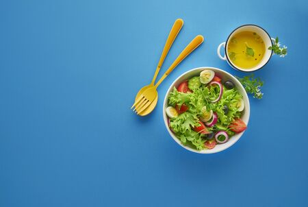 Fresh green vegetable salad with lettuce, tomatoes and cucumber in white bowl on blue background with orange spoon and fork, healthy eating and dieting concept, top view with copy space Banque d'images