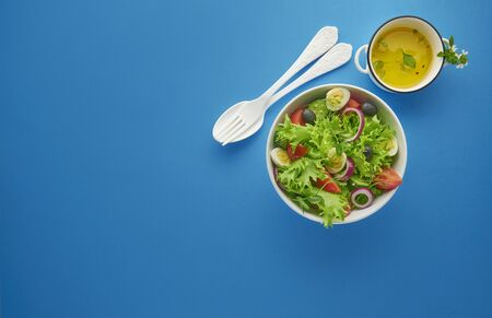 Fresh green vegetable salad with lettuce, tomatoes and cucumber in bowl on blue background with white spoon and fork, healthy eating and dieting concept, top view with copy space