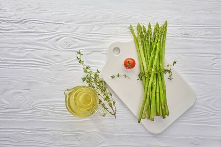 Bunch of fresh green asparagus on white ceramic board with organic olive oil and herbs on white wooden table, healthy vitamin eating and vegan cooking concept, top view with copy space Banque d'images