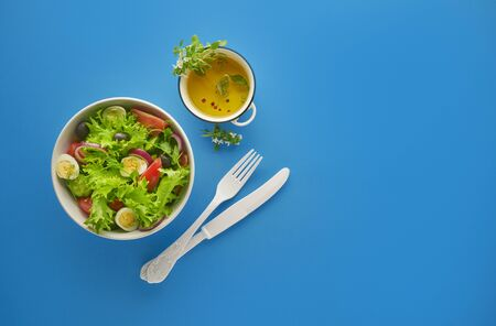 Fresh green vegetable salad with lettuce, tomatoes and cucumber in bowl on blue background with white knife and fork, healthy eating and dieting concept, top view with copy space