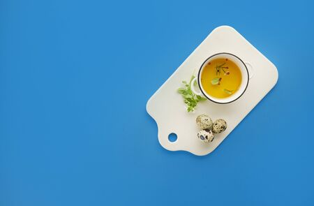 Organic olive oil in white ceramic board over blue background with top view, copy space, healthy food concept