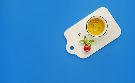 Organic olive oil with spices in white ceramic board over blue background with top view, copy space, healthy food concept Banque d'images