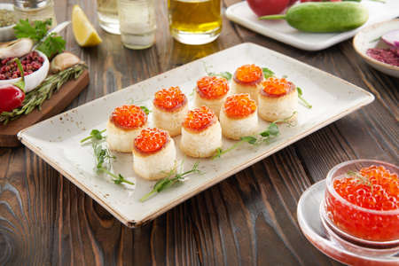 Tartlets or canape with red caviar and ingredients on wooden table, cooking concept