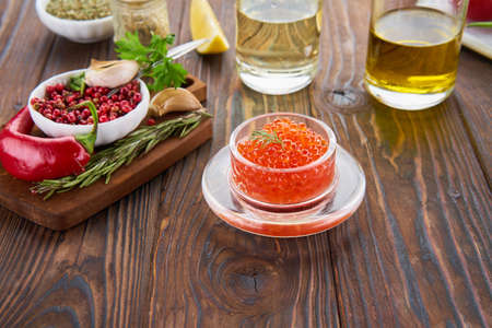 Composition with red caviar in the glass jar on the wooden table and ingredients for cooking