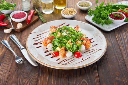 Fresh healthy avocado and shrimps salad with arugula, tomatos and cheese on wooden background, cooking concept with ingredients