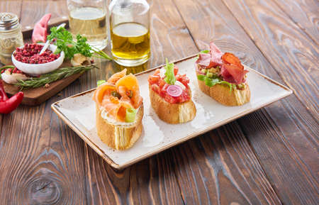 Bruschetta with various toppings, variety of small sandwiches with salmon red fish, fresh vegetables, tomatos and herbs on wooden table, diet food ingredients background. Banque d'images