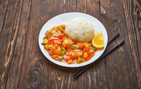 Sweet and sour chicken in orange sauce with vegetables, rice and chopsticks on wooden background