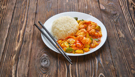 Sweet and sour chicken in orange sauce with vegetables, rice and chopsticks on wooden background, asian food concept with copy space