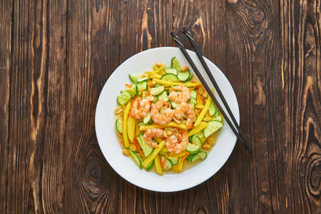 A spicy mango salad with vegetables, chili and shrimps, chopsticks on wooden background, asian food concept top view with copy space
