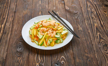 A spicy mango salad with vegetables, chili and shrimps, chopsticks on wooden background, asian food concept with copy space