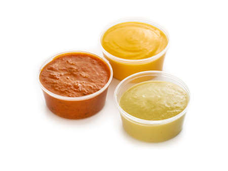 Plastic containers with sauces ketchup, mustard and cheese on white background, take away fast food delivery concept