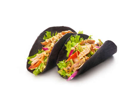 Chicken tacos with vegetables, red onion and bell peppers in black tortillas bread on white background, mexican fast food concept