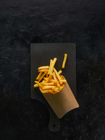 French fries in a craft paper box on wooden board and black background, top view with copy space