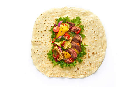 Opened tortilla wrap sandwich with juicy steak, grilled vegetables, cherry tomatoes, lettuce salad and herbs on white background, top view