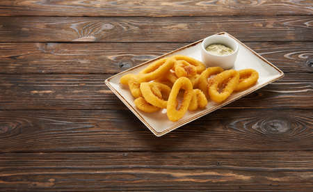 Deep fried calamari or squid rings with sauce on wooden background with copy space