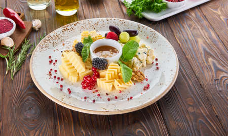 Cheese plate served with sauce, mint, nuts and fresh berries on a wooden background Banque d'images