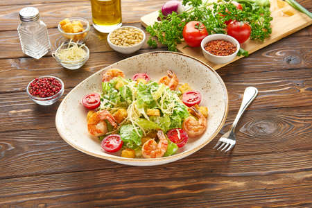 Shrimp caesar salad with parmesan cheese, croutons, lettuce and cherry tomatoes, with a fork in a white bowl plate on a wooden rustic background texture with ingredients Banque d'images