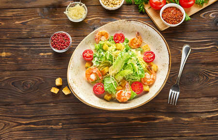 Shrimp caesar salad with parmesan cheese, croutons, lettuce and cherry tomatoes, with a fork in a white bowl plate on a wooden rustic background texture, top view with ingredients Banque d'images