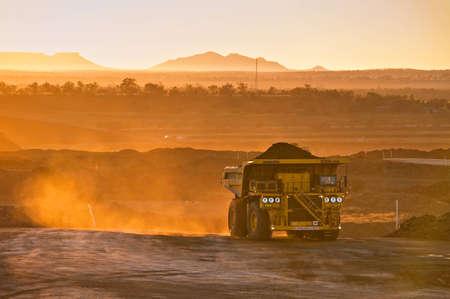 Ciężarówka górnictwa węgla kamiennego w pomarańczowym świetle poranka