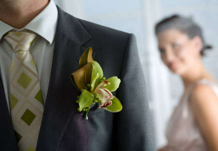 buttonhole: Husband wearing a corsage and standing in front of the Bride