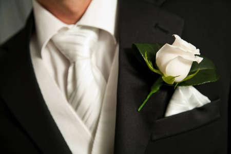 buttonhole: Close up of a white rose corsage on a Groom with a white tie and waistcoat Stock Photo