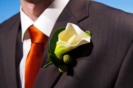 buttonhole: Close up of a lily corsage on a groom with blue sky in background