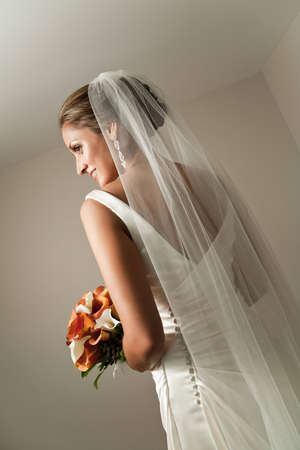 looking away from camera: Beautiful bride from behind showing her veil and bouquet, looking away from camera