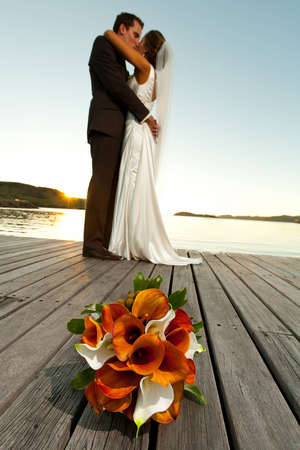 wedding bouquet in foreground and newlyweds kissing behind at sunset photo