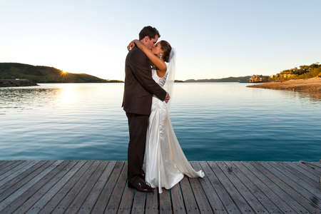Newlyweds kissing on a jetty at sunset with beautiful water behind photo