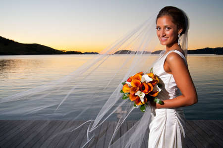 Beautiful bride with veil extended at sunset holding her bouquet Stock Photo - 12504052
