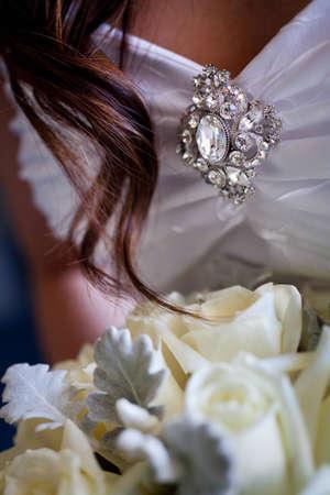 Detail van broche op een trouwjurk, met een haarlok en het boeket in de schoot