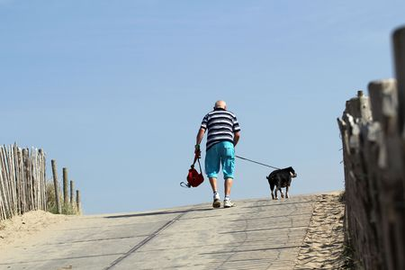 Old, lonely man is happy walking his dog in the sun