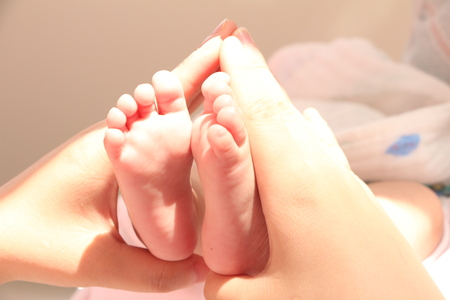 baby feet on mothers hand