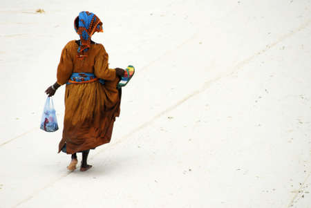 mauritius: Colourfully dressed lady walking on the beach after having shopped at fishing boats returning from deep sea