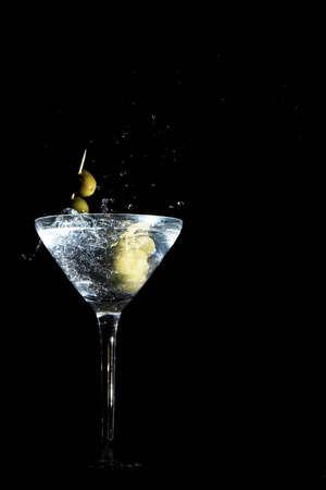 martini splash: Two calamata olives on a toothpick dropped into a martini glass