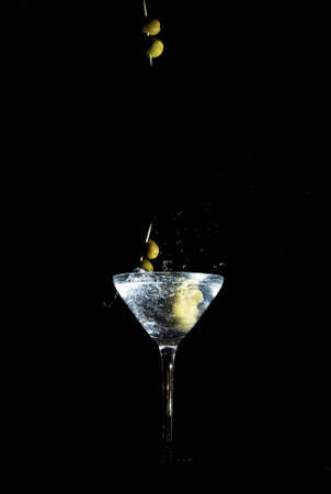tilted: Two calamata olives on a toothpick dropped into a martini glass