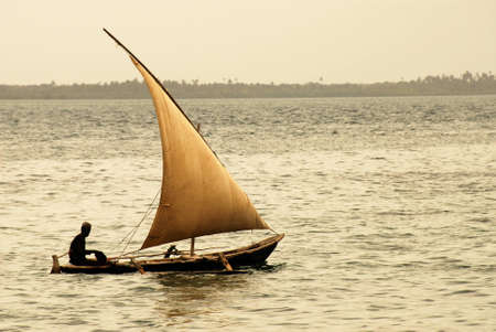 going out: Fisherman going out to sea at dusk on Zanzibar Island off the coast of Tanzania, Africa Stock Photo