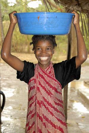 africa child: Young Swahili girl collecting rain water on Chole Mjini Island near Zanzibar Island, Tanzania
