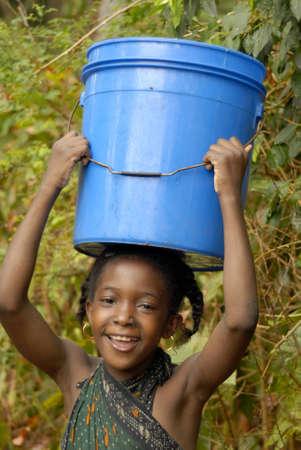 water bucket: Young Swahili girl carrying rain water on Chole Mjini Island near Zanzibar Island, Tanzania